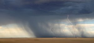 Lightning storm sweeps across a tan prairie.