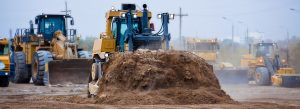 A yellow bulldozer moves dirt amid other heavy equipment on a construction site.