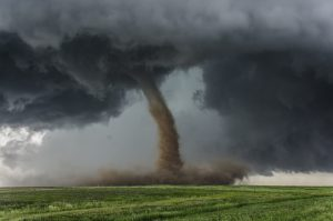 tornado funnel spins in a cloud of dust over a green prairie. Protect your home from acts of God and the unpredictable Kansas weather.